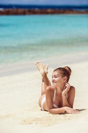 31807716 - beautiful woman lying on sea shore in bikini