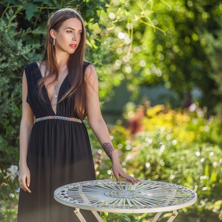42490500 - outdoors portrait of beautiful young woman in luxury black dress posing in summer garden.