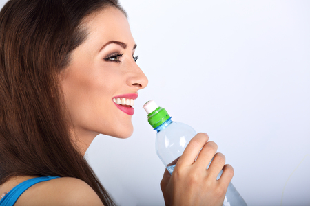 81995924 - beautiful happy toothy smiling makeup woman profile holding and drinking water from the bottle. healthy face skin. closeup portrait.